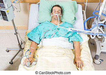 High angle view of critical patient with endotracheal tube resting on bed in hospital