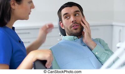 patient with toothache at dentist office - medicine,...