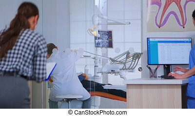 Patients asking for help filling in dental registration form preparing for exemination. Senior woman sitting on chair in waiting area of crowded orthodontist office while doctor working in background