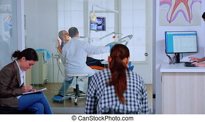 Patients asking informations filling in dental document preparing for teeth exemination. Senior woman sitting on chair in waiting area of crowded orthodontist office while doctor working in background