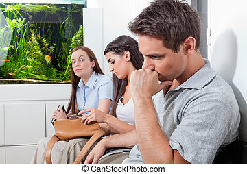 Patients In Doctor's Waiting Room - Three patients sitting...