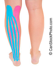 Patients leg with applied pink and blue kinesio tape on...