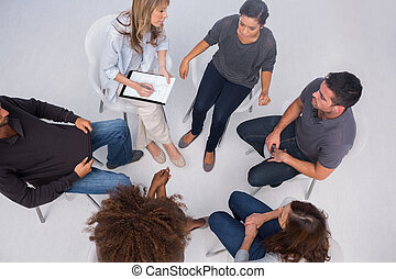 Patients listening to each other in group session sitting in...