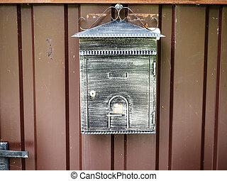 Patina mailbox hanging on a brown iron door