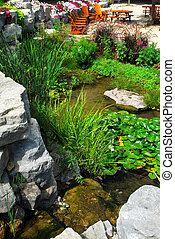 Natural stone pond and patio landscaping with aquatic plants