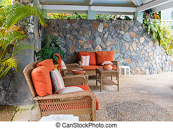 A nice stone patio with wicker furniture and orange cushions