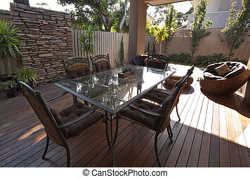 Modern patio with outdoor dining table and chairs. Polished timber decking. Perfect for summer entertaining.