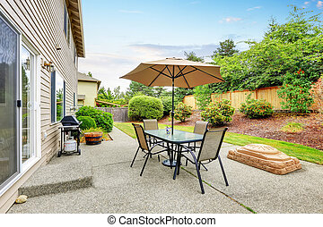 Patio table set with umbrella in the back yard.