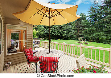 Patio table with yellow umbrella on walkout deck