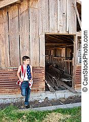Patriotic boy and old barn