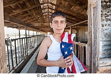 Patriotic boy in old barn