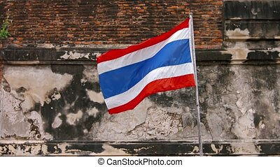 Video UltraHD 3840x2160 - Thai Flag, with its alternating red, white and blue stripes, flutters cheerfully in the breeze from its wall-mounted pole in Ayutthaya, Thailand.