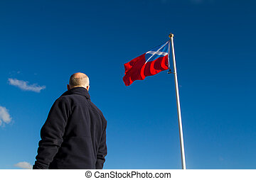 Patriotic man looking at Scotland flag