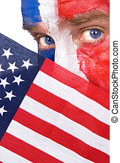 Patriotic man peering over an American flag