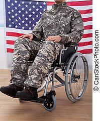 Patriotic Soldier Sitting On Wheel Chair Against American Flag