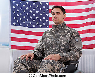 Patriotic Soldier Sitting On Wheel Chair Against American...