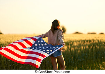 Patriotic woman walking at sunset field, holding with open arms American national flag.