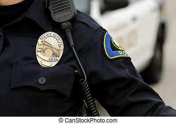 a close up of an officers badge and uniform