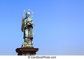 Saint Nepomuk, patron of bridges on charles bridge over river Vltava at the spot where he was thrown into it