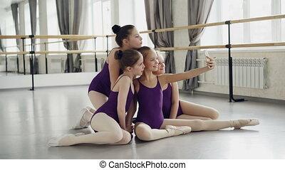 patrząc, balet, smartphone, school., podłoga, selfie, posiedzenie, dziewczyny, leotards, dancehall, radosny, znowu, aparat fotograficzny, przedstawianie, wpływy, złamanie, podczas, dzieci