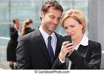 patrząc, telefon, koledzy, handlowy