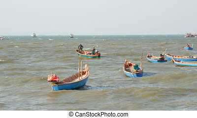 PATTAYA, THAILAND - DECEMBER 25, 2017: Small fishing boats sail along the lush sea on the waves. Fishermen catch fish in sea