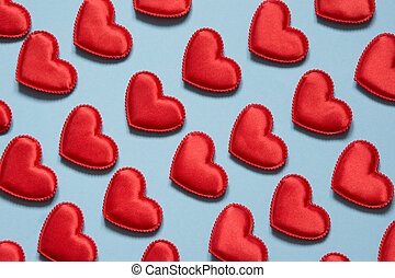 Pattern made of red hearts on blue. Heart in isometric style. Valentine's card. May be use for wrapping paper.