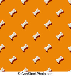 pattern made with marmalade in form of bone on bright orange background.