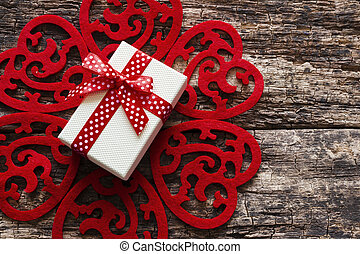pattern of red hearts with a gift box in the middle on a wooden background