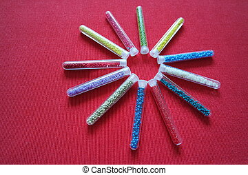 pattern of tubes with small beads sun red background