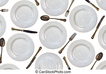 Pattern of vintage dinner plates, knives, forks and spoons