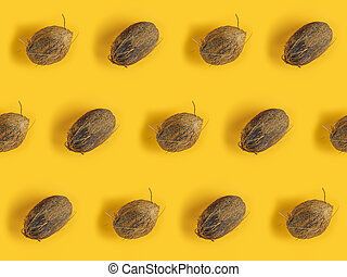 Pattern with ripe coconuts on yellow background. Top View. ...