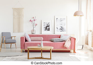 Patterned armchair and pink couch in feminist apartment...