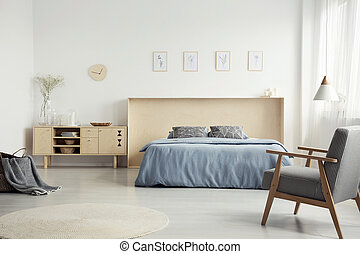 Patterned armchair in bright bedroom interior with wooden cupboard next to blue bed. Real photo