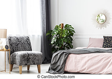 Patterned armchair near bed and plant in cozy bedroom interior with round gold mirror