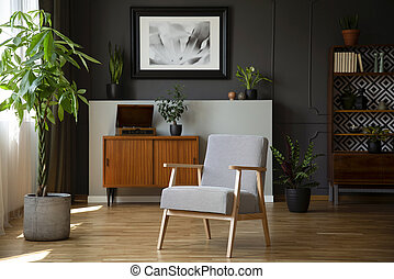 Patterned armchair next to plant in grey living room interior with poster above cabinet. Real photo