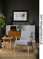 Patterned armchair next to wooden table in dark grey living room interior with poster. Real photo
