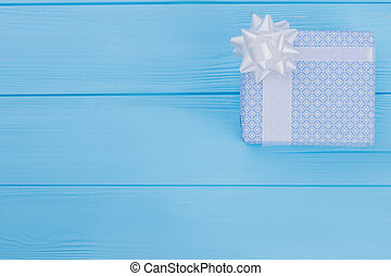 Patterned blue gift box on wood with copyspace.