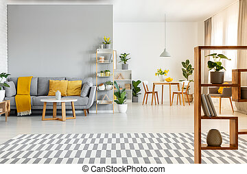 Patterned carpet and table in spacious apartment interior with yellow cushions on grey couch. Real photo