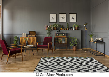 Patterned carpet in grey living room interior with dark red wooden armchairs and posters. Real photo