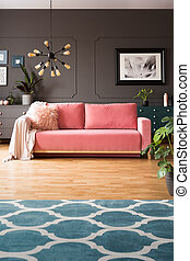 Patterned carpet in grey living room interior with lamp and poster above pink sofa. Real photo