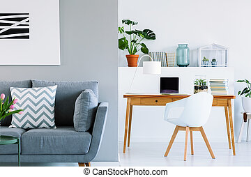 Patterned cushion on grey sofa in scandinavian home office interior with chair at desk. Real photo