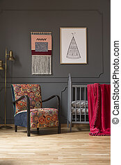 Patterned floral armchair next to baby's bed in bedroom interior with poster on grey wall. Real photo