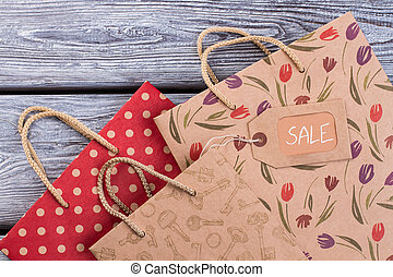 Patterned gift bags on wooden background.