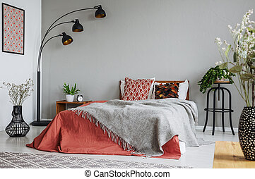 Patterned pillow and grey blanket on king size bed with dark orange duvet in luxury bedroom interior in elegant apartment, real photo with copy space on the wall