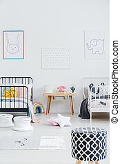 Patterned stool in bright kids bedroom interior with posters above black and white bed. Real photo