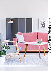 Patterned wooden armchair next to table and pink sofa in living room interior with poster. Real photo