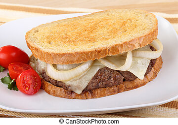 Sandwich with hamburger, onion, and cheese on rye bread with grape tomatoes on the side