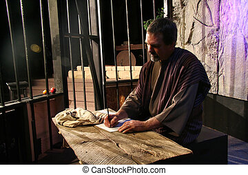 Paul is writing his epistles in the prison cell in this church production