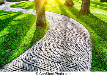 Paved footpath in spring park - Paved footpath in green ...
